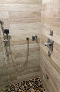 Horizontal tiled shower with rock bottom